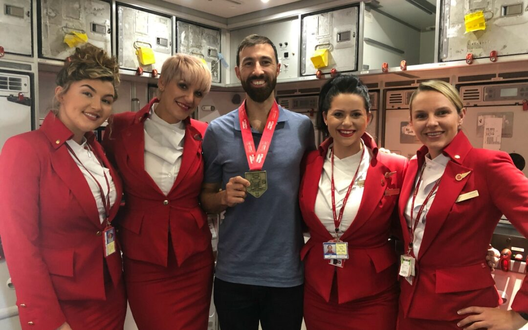 Adam wearing his marathon medal on a plane posing with flight attendants