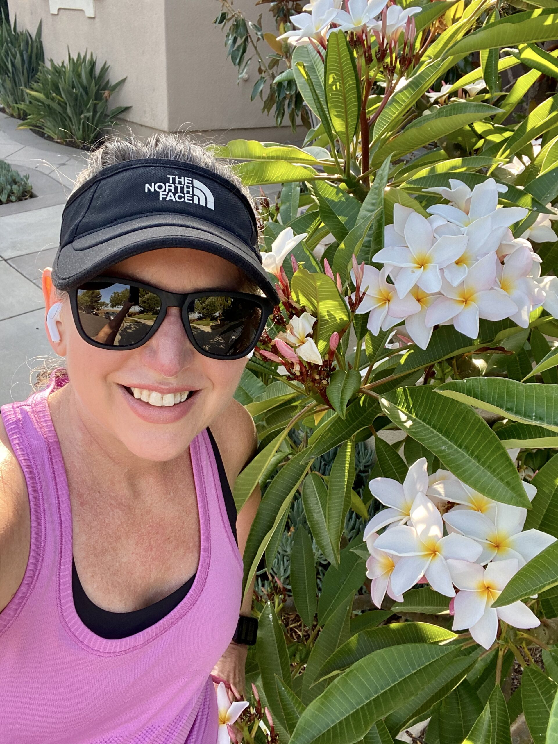 Amy on a run in front of a large plumeria tree in bloom