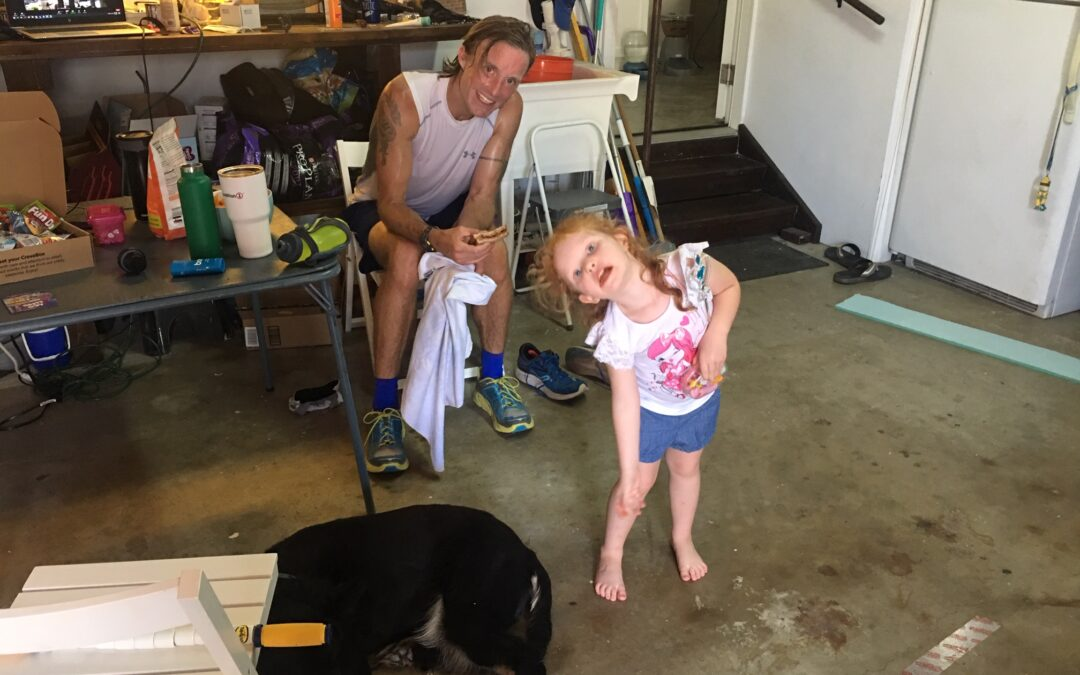 Ben taking a break in the garage with daughter Sasha and their dog