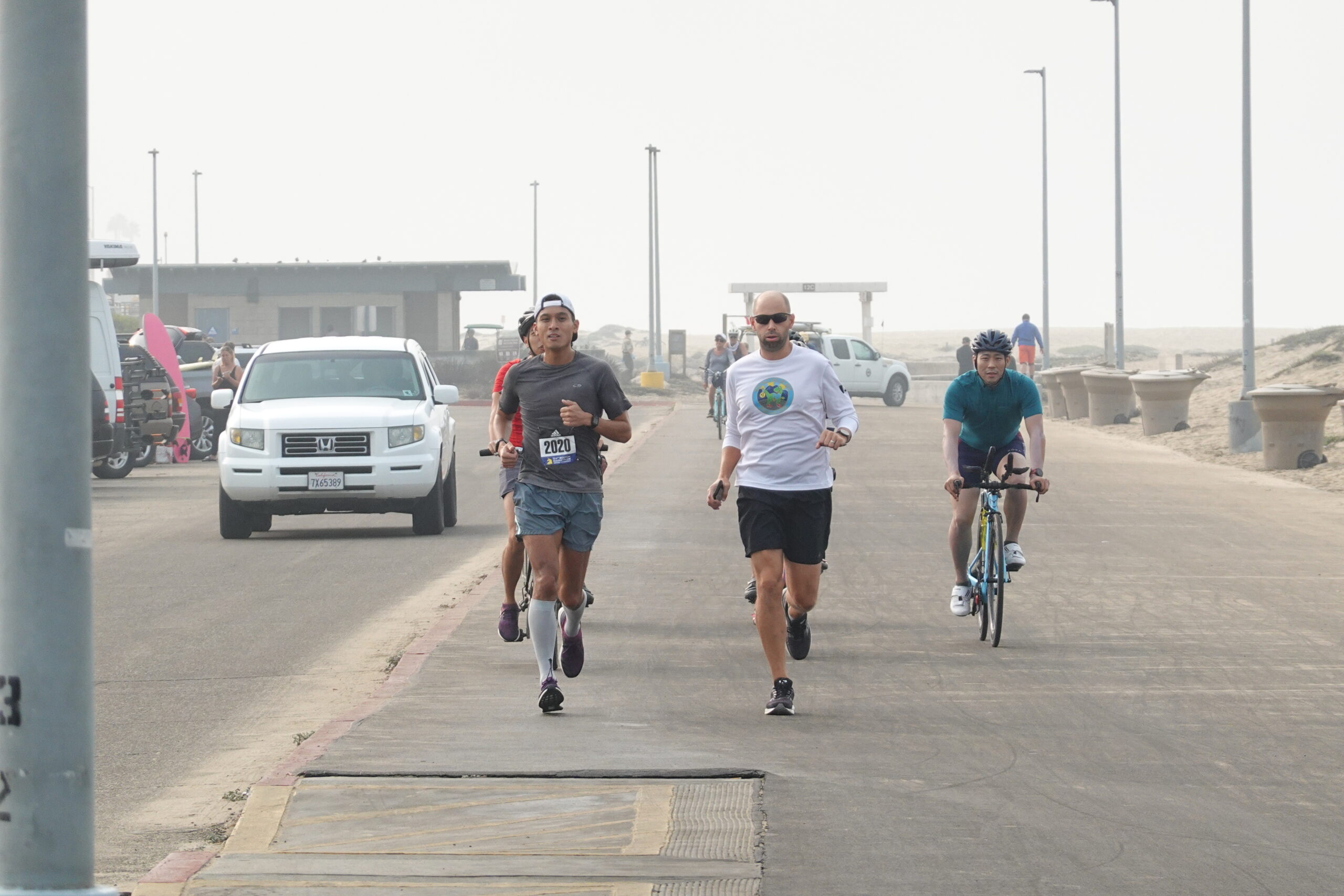 Justin running with another runners and cyclists on the beach bike path