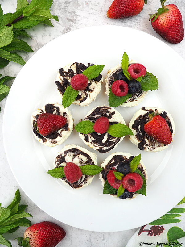 Plate of chocolate marble mini cheesecakes garnishes with berries and mint