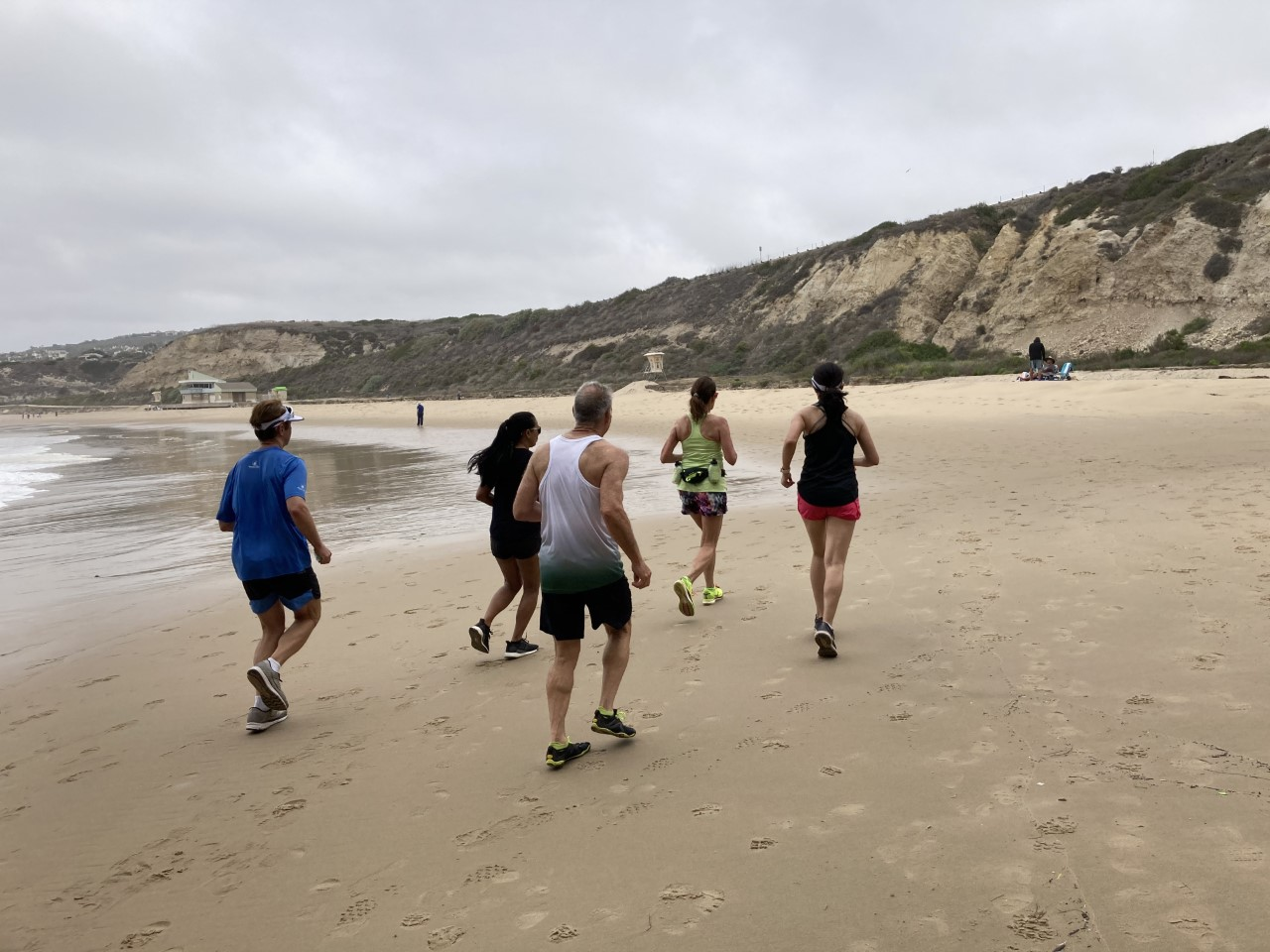 Runners running on the sand in Crystal Cove